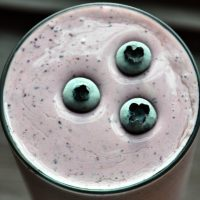 Shot of the top of a glass of our Blueberry Maple Protein Shake topped with fresh blueberries