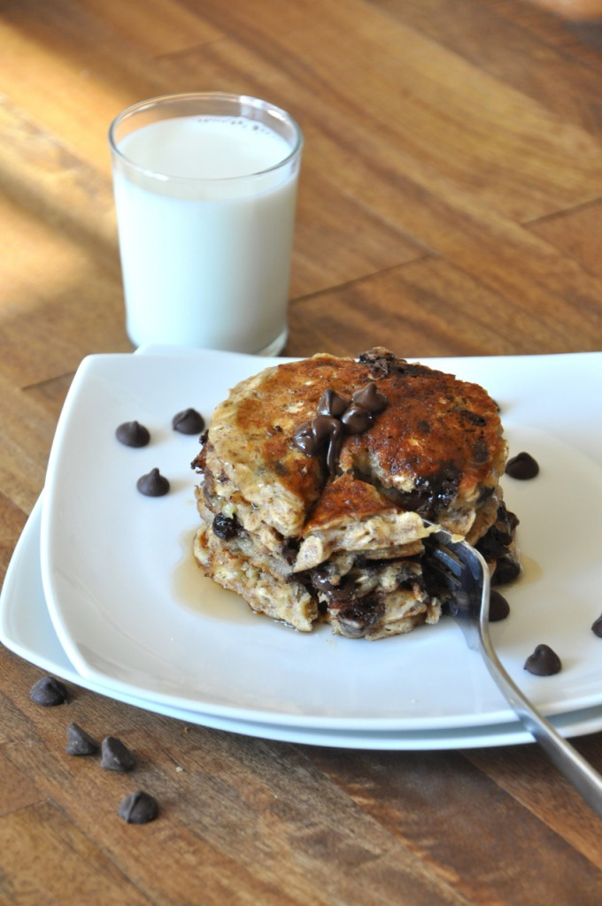 Using a fork to cut into a stack of our incredible vegan Chocolate Chip Oatmeal Pancakes recipe