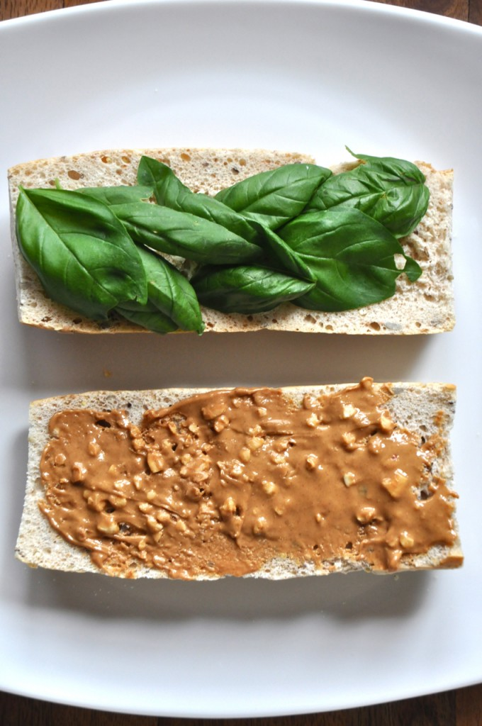 Plate with two slices of bread topped with basil on one and peanut butter on the other