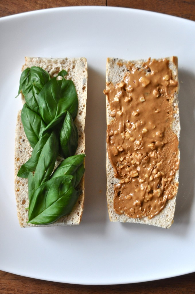 Slices of bread topped with fresh basil and peanut butter for making a healthy vegan sandwich