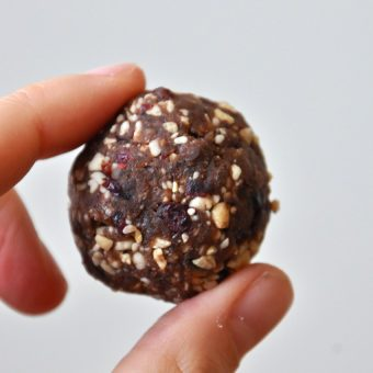 Holding up a bite of dough for our Chocolate Cashew Cookie Larabar Pops recipe