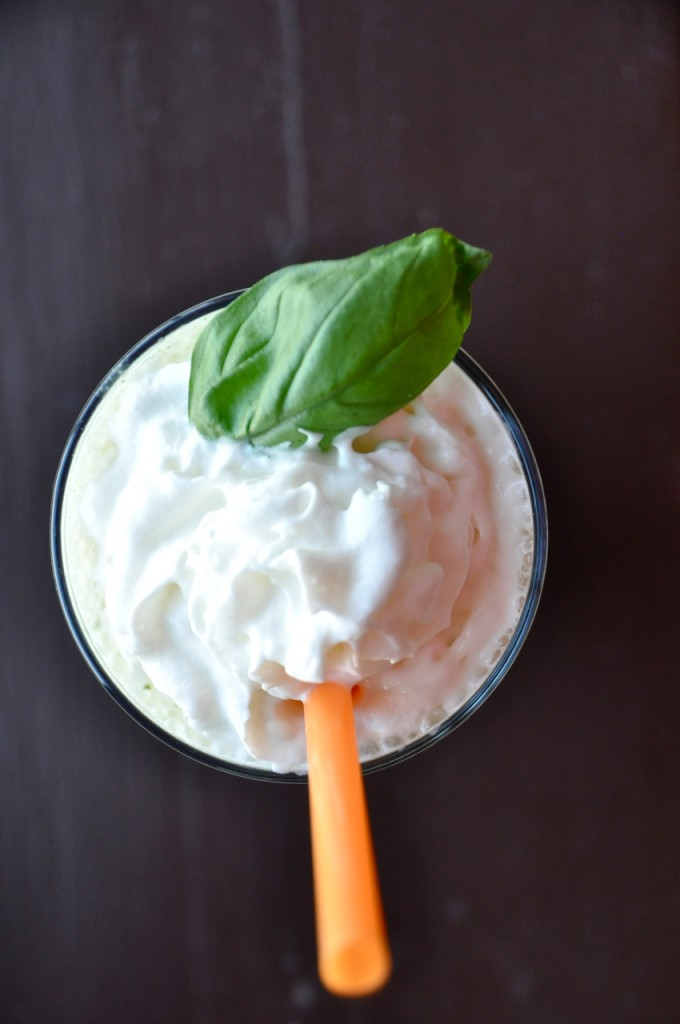 Top down shot of a Peanut Butter and Basil Milkshake topped with whipped cream