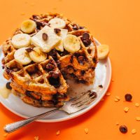 Chocolate Chip Banana Bread Waffles topped with sliced bananas and chocolate chips