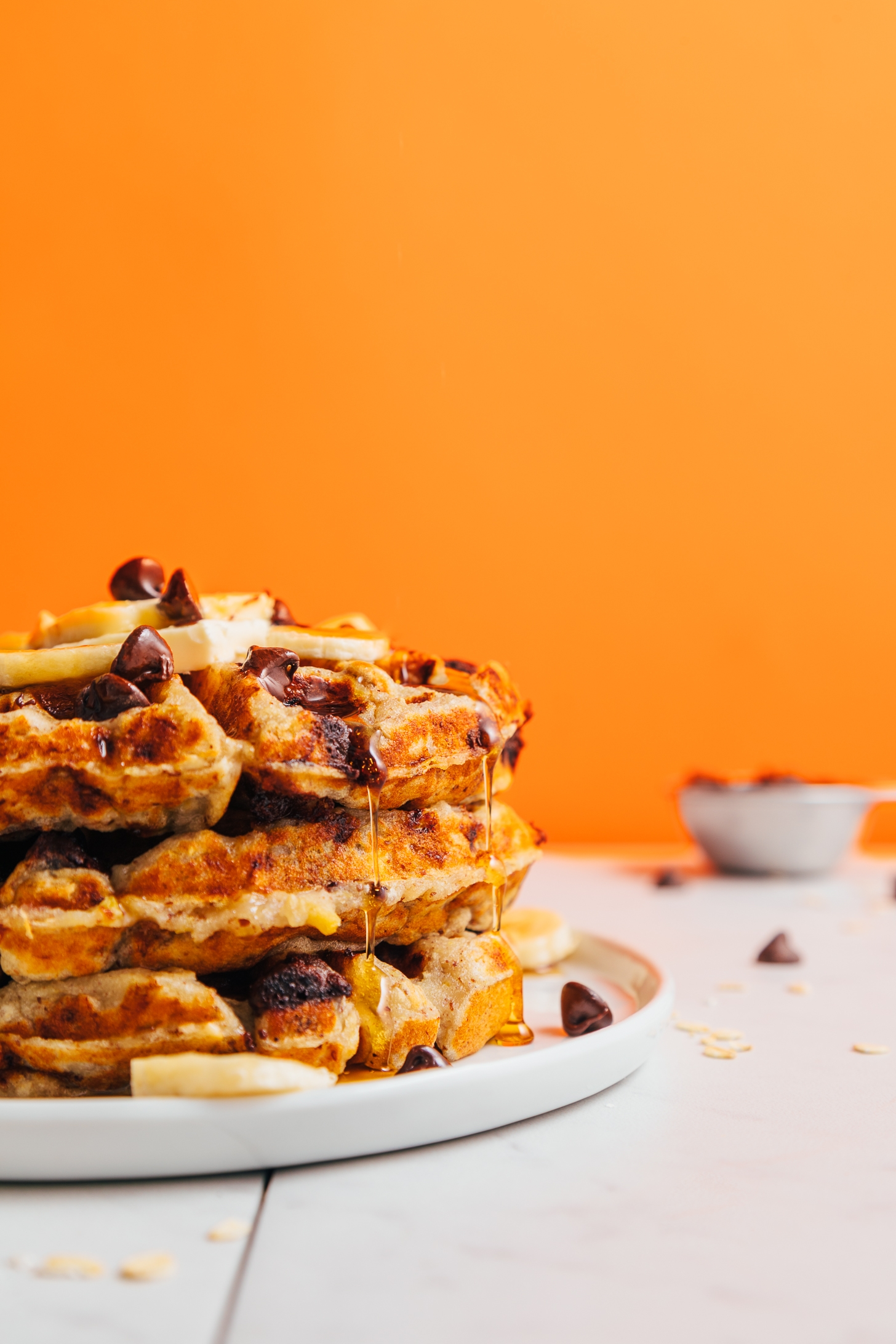 Maple syrup dripping off a stack of Chocolate Chip Banana Bread Waffles