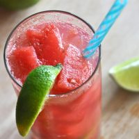 Tall glass of our Watermelon Limeade Cocktail recipe with a lime wedge on the rim