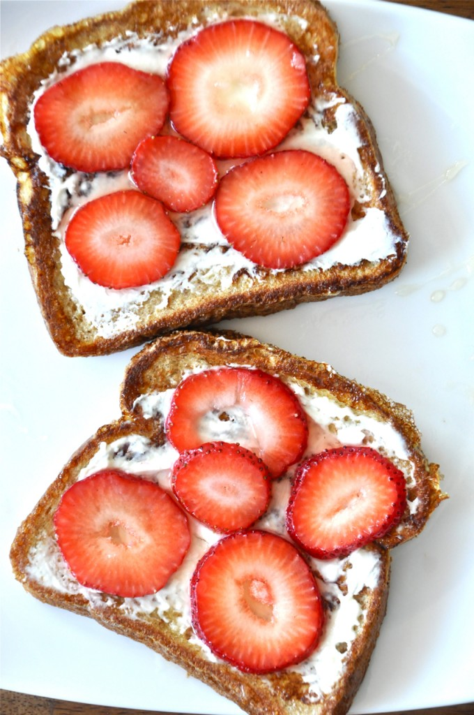 Plate with slices of toast topped with cream cheese and strawberries