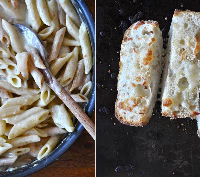Pan of our Healthy Alfredo Sauce alongside a baking sheet with slices of garlic bread