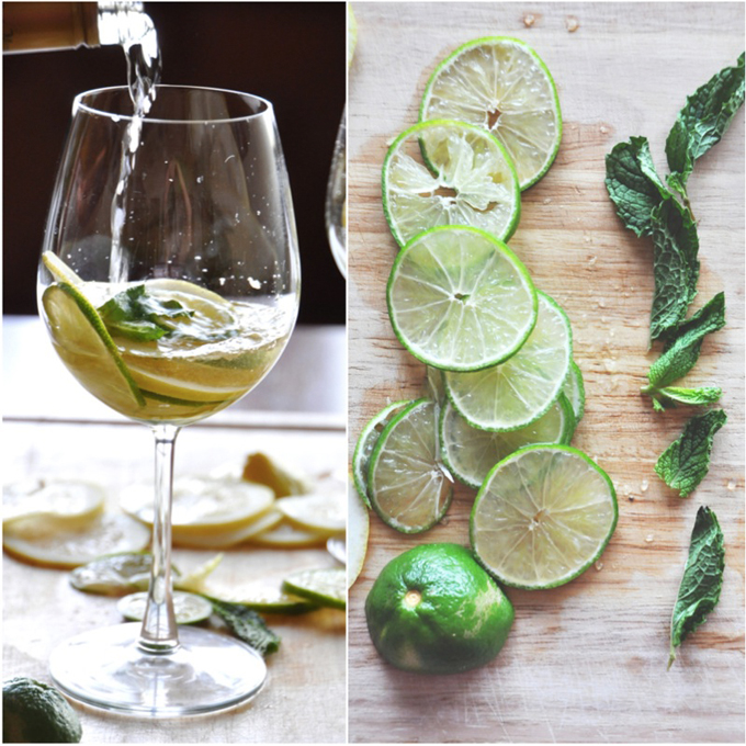 Pouring white wine into a glass of citrus and mint for a simple homemade Sangria recipe