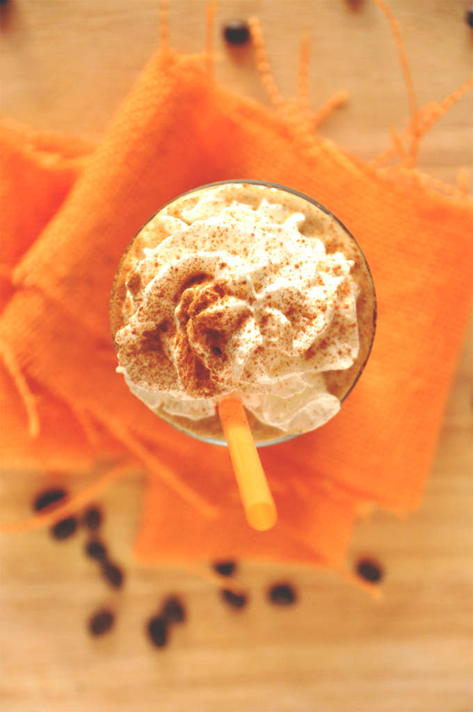 Top down shot of a glass of Pumpkin Frappuccino topped with whipped cream and cinnamon