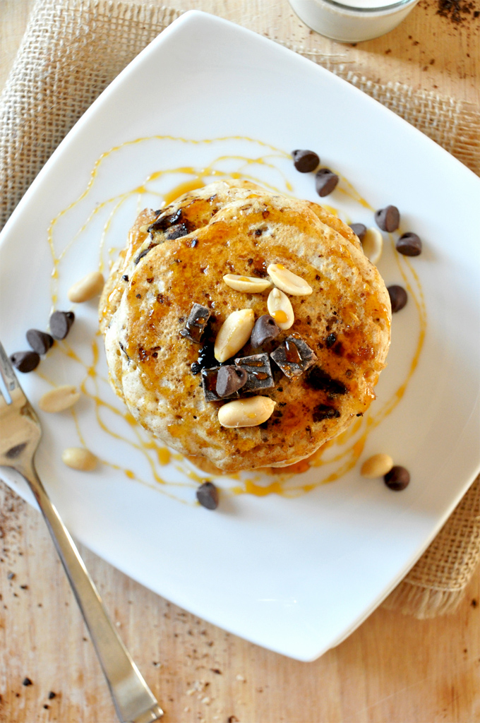 Tall stack of Vegan Snickers Pancakes topped with dark chocolate and peanuts