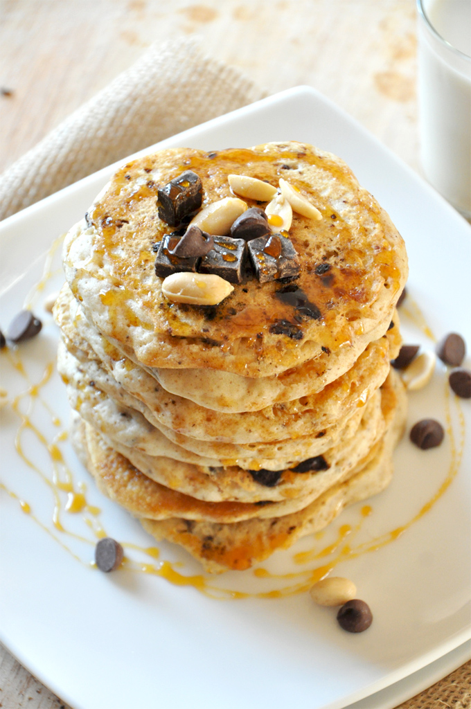 Tall stack of our Vegan Snickers Pancakes recipe topped with peanuts and dark chocolate