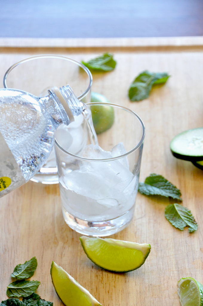 Pouring tonic water into glasses to make our Cucumber Cooler Cocktails recipe
