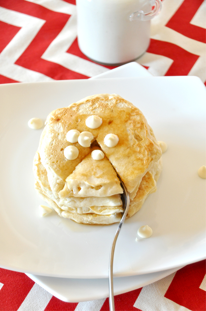 Using a fork to cut into a stack of White Chocolate Macadamia Nut Pancakes