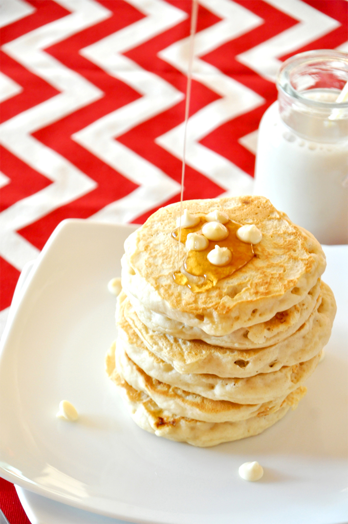Drizzling syrup onto a stack of homemade White Chocolate Macadamia Nut Pancakes