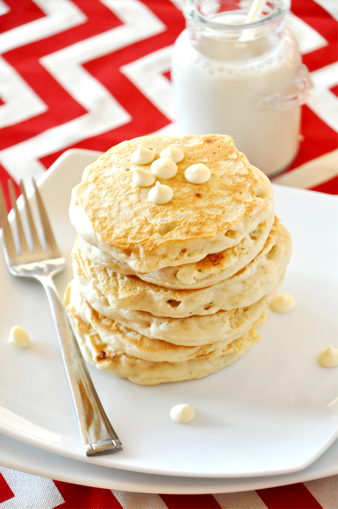 Tall stack of White Chocolate Macadamia Nut Pancakes with a jar of soy milk