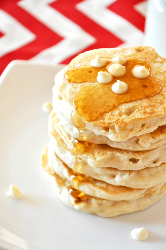 Tall stack of White Chocolate Macadamia Nut Pancakes topped with syrup and chocolate chips