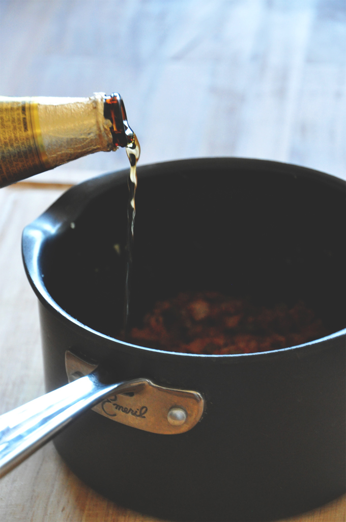 Pouring beer into a large saucepan to make Vegan Beer Chili