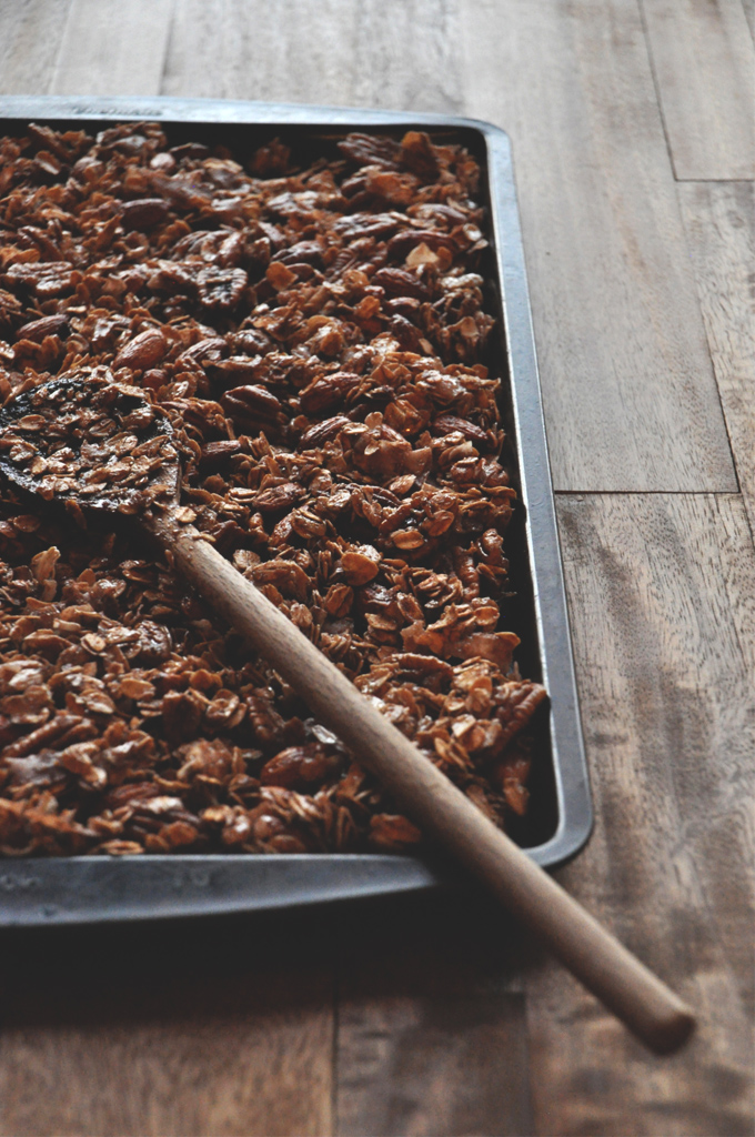 Stirring a baking pan filled with a batch of our Nut and Honey Coconut Granola recipe