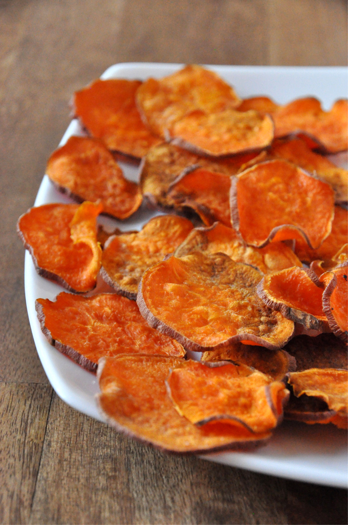 Plate of homemade sweet potato chips sliced with a knife