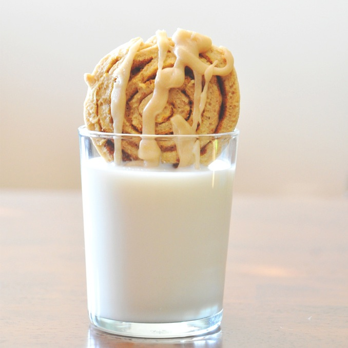 Dipping a Pumpkin Cinnamon Roll Cookie into a glass of dairy-free milk