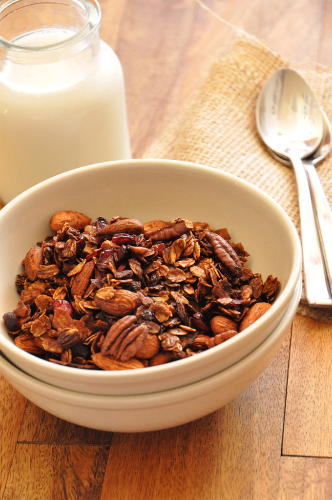 Bowl of Nut and Honey Coconut Granola alongside a glass of almond milk