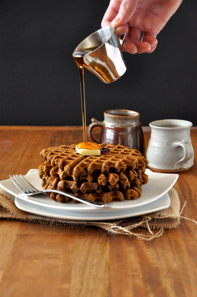 Pouring syrup onto a stack of Vegan Gingerbread Waffles