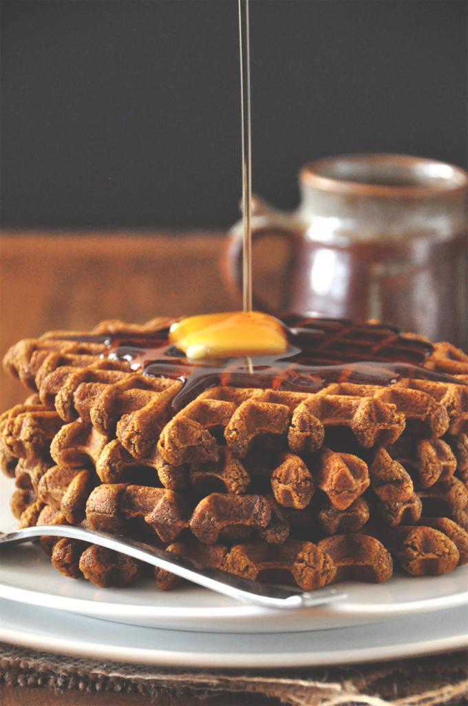 Drizzling syrup onto a slab of vegan butter perched on top of delicious homemade Gingerbread Waffles