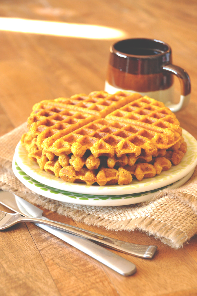 Stack of homemade Vegan Pumpkin Cornbread Waffles alongside a mug of coffee