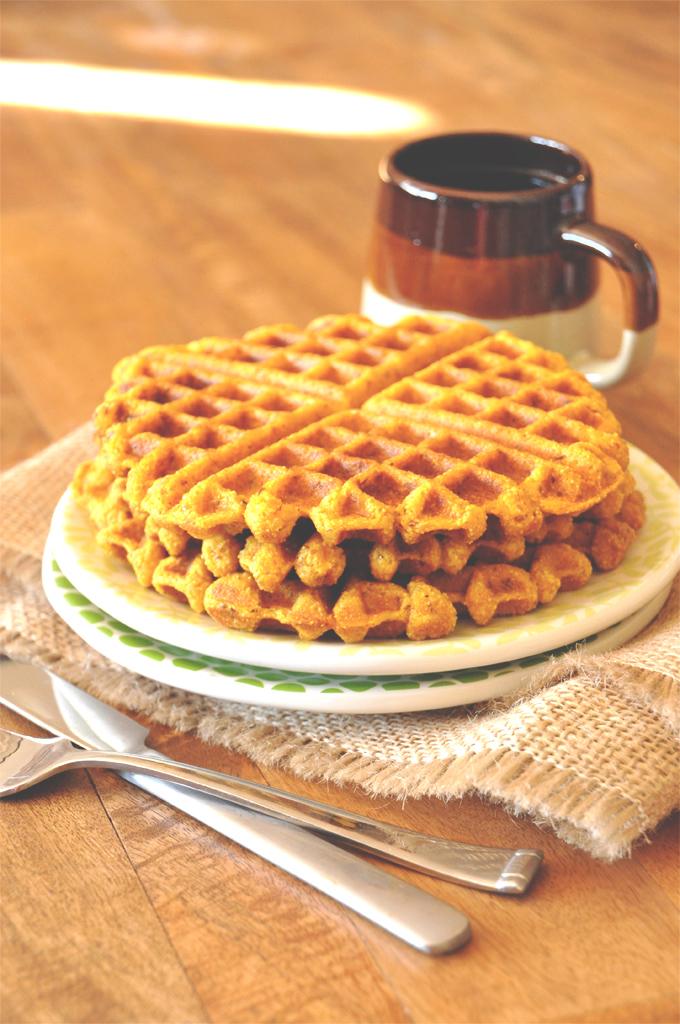 Stack of homemade Vegan Pumpkin Cornbread Waffles alongside a mug of coffee