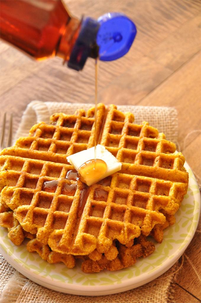 Drizzling syrup onto a batch of our Vegan Pumpkin Cornbread Waffles recipe