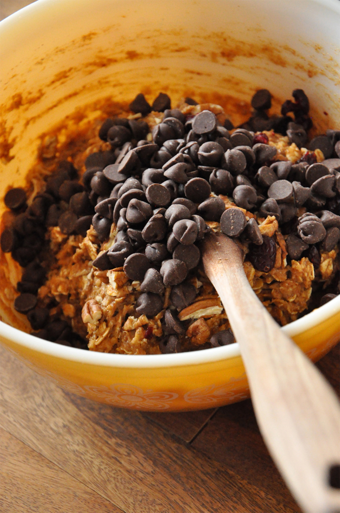 Stirring chocolate chips into a bowl of our Vegan Everything Breakfast Cookie dough