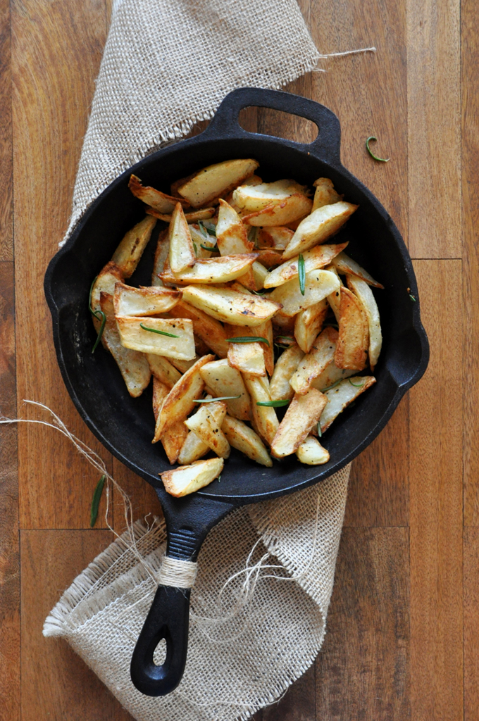 Cast-iron skillet of homemade Crispy Baked Rosemary Garlic Fries