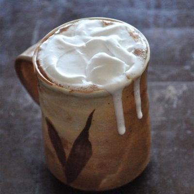 Overflowing mug of Mexican Hot Chocolate with Coconut Whipped Cream