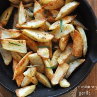 Bowl filled with homemade Crispy Baked Rosemary Garlic Fries