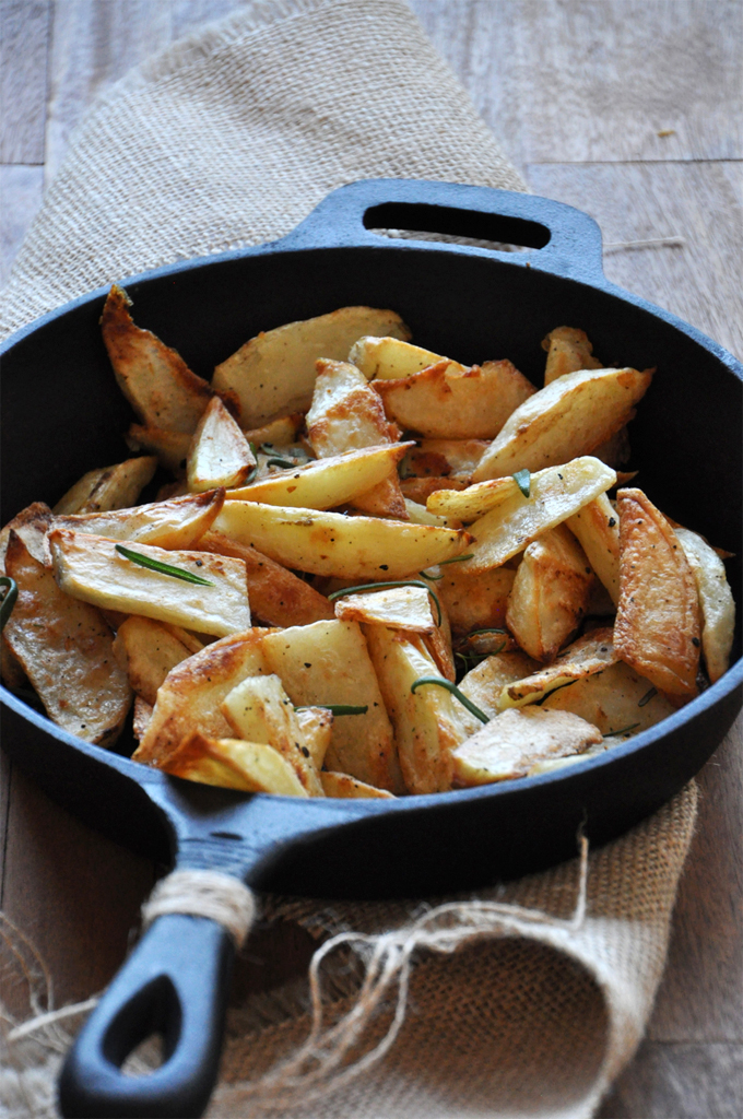 Batch of our Crispy Baked Rosemary Garlic Fries recipe in a cast-iron skillet