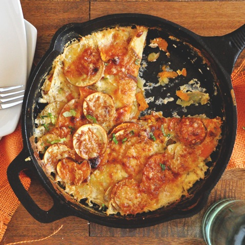Skillet of Sweet Potato Parmesan Gratin with a slice removed