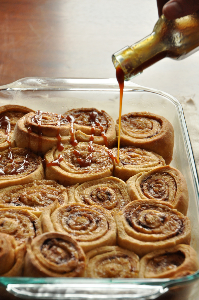 Pouring caramel sauce over a batch of our Overnight Honey Wheat Cinnamon Rolls recipe