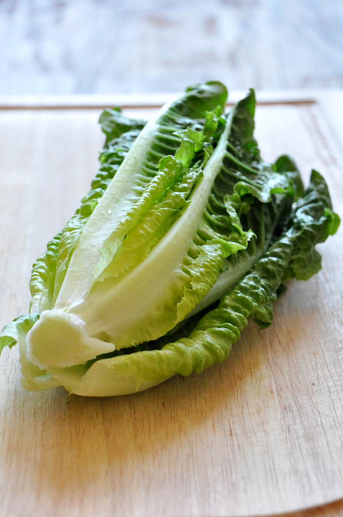 Cutting board with a head of romaine lettuce for making a Broiled Romaine Salad