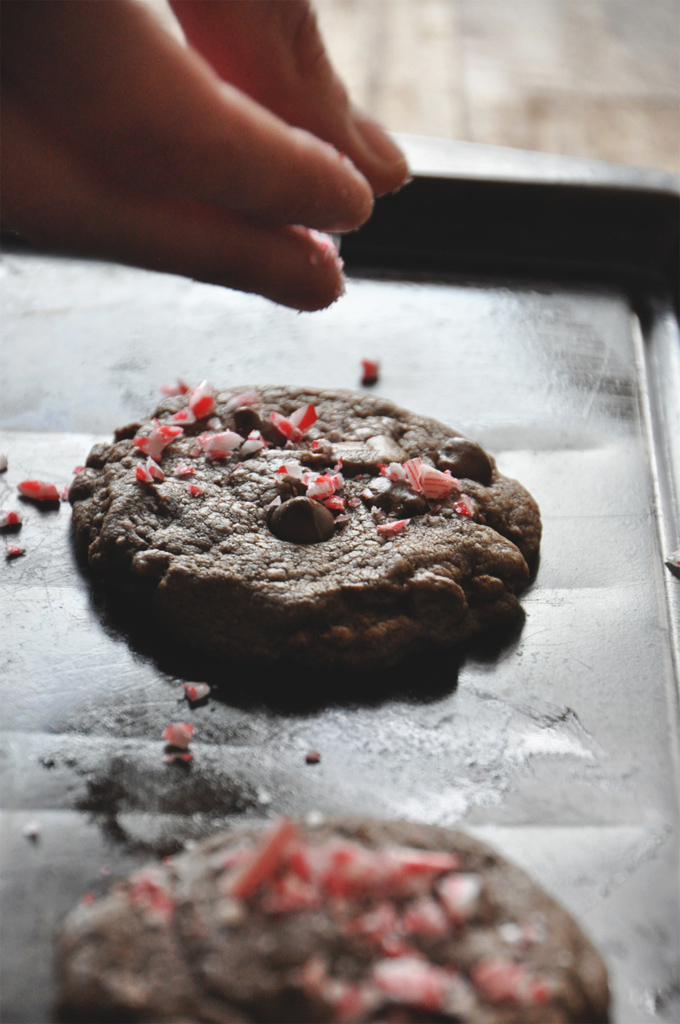 Sprinkling crushed candy cane onto a Chewy Double Chocolate Peppermint Cookie