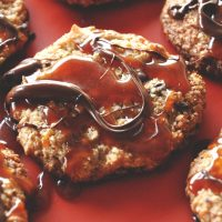 Batch of Gluten-Free Bourbon Caramel Samoa Cookies on a red background
