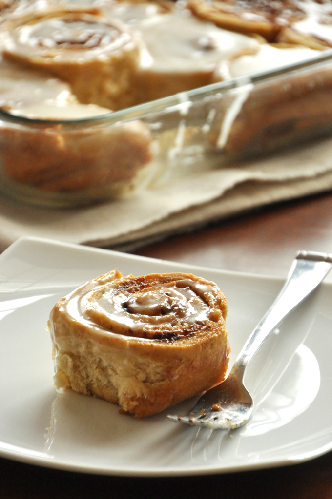 Delicious Overnight Honey Wheat Cinnamon Rolls on a plate and in a baking pan