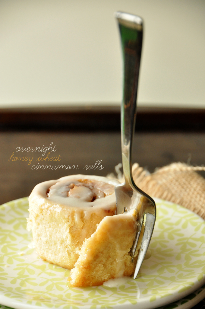 Using a fork to grab a bite of one of our Overnight Honey Wheat Cinnamon Rolls