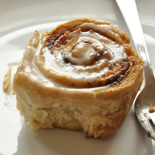 Close up shot of a homemade Honey Wheat Cinnamon Roll topped with icing