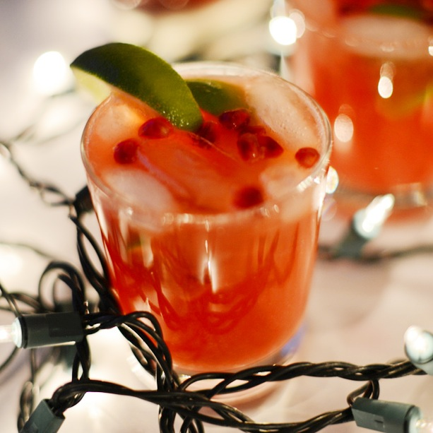 Glasses of homemade Pomegranate Lime Spritzers surrounded by Christmas lights