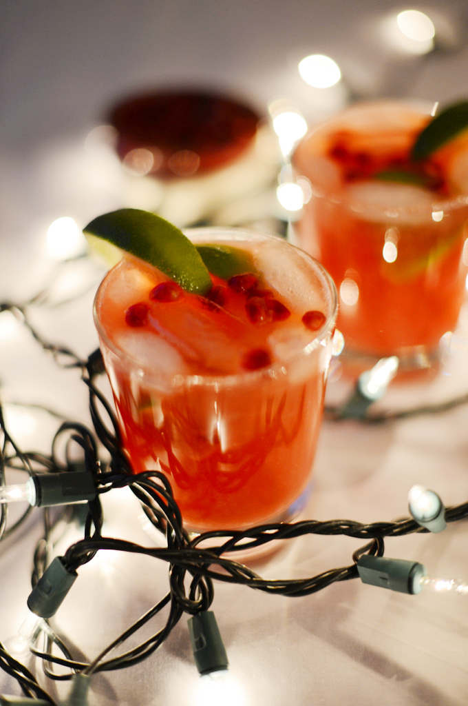 Glasses of Pomegranate Lime Spritzers surrounded by Christmas lights