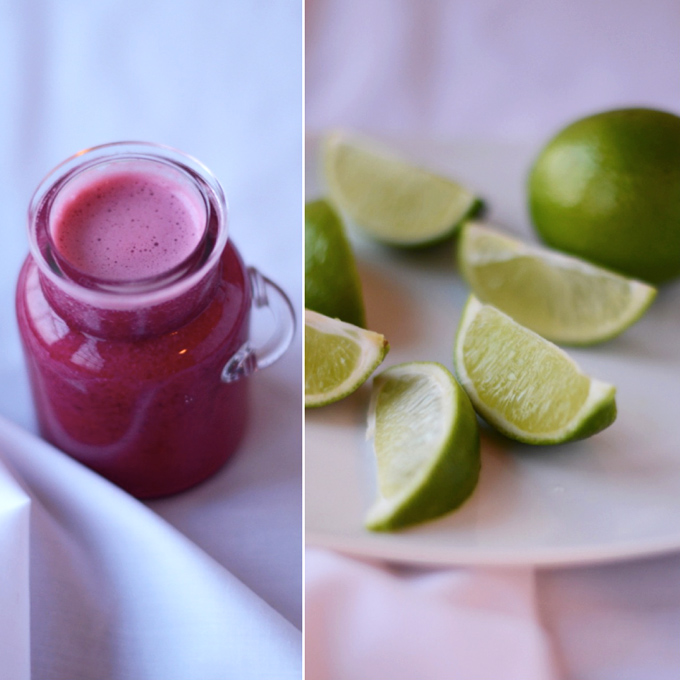 Jar of pomegranate juice and fresh lime wedges for making Pomegranate Lime Spritzers