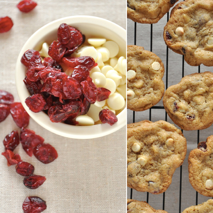 Bowl of white chocolate chips and dried cranberries alongside a cooling rack of freshly baked cookies