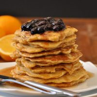 Plate stacked high with Whole Wheat Griddle Cakes topped with Blueberry Orange Compote and maple syrup