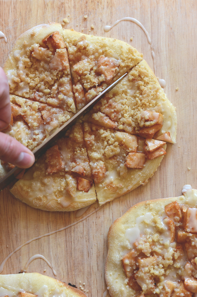 Using a large knife to cut an Apple Streusel Breakfast Pizza into bite-sized pieces