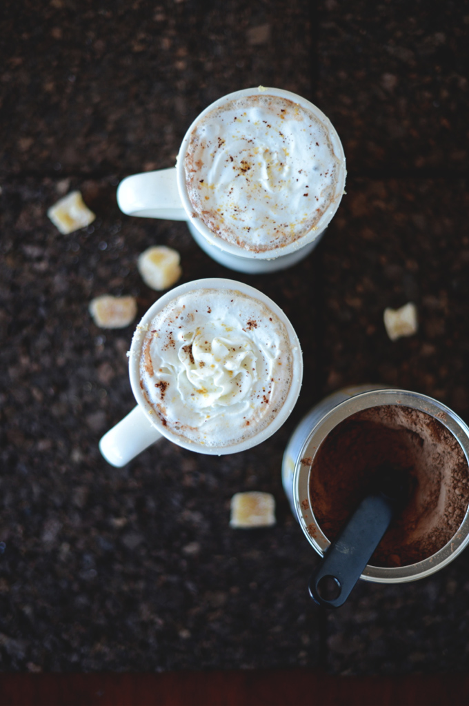 Two mugs of dairy-free Ginger Hot Chocolate and a container of cocoa powder